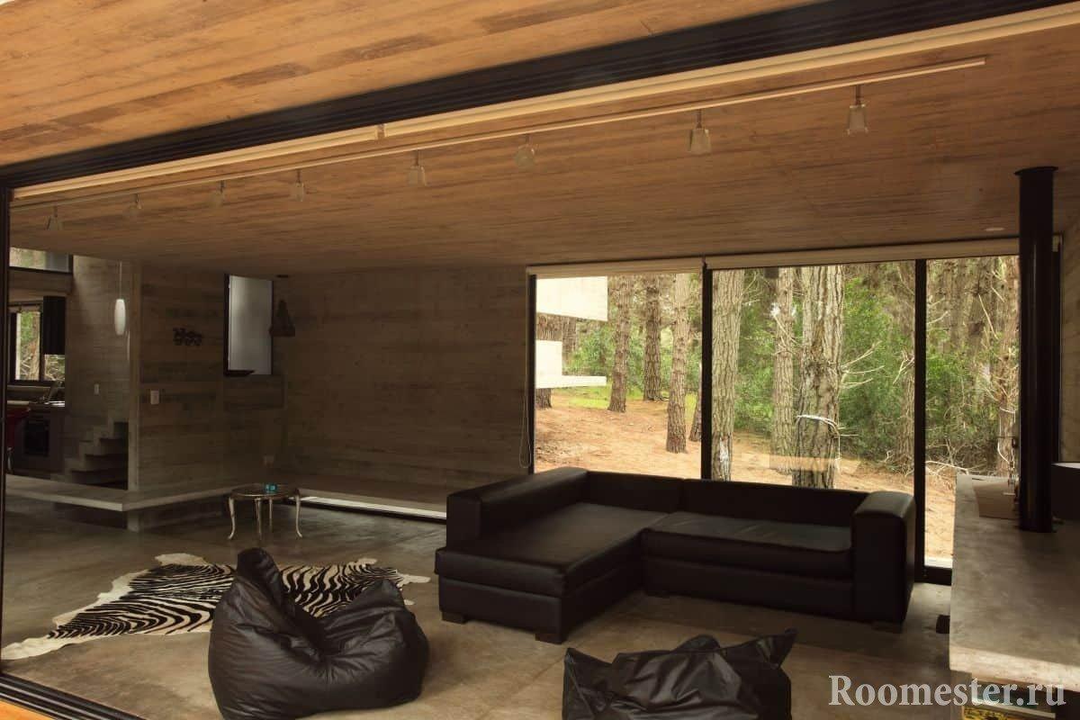 Гостиная с отделкой под дерево в деревянном доме с панорамным окном