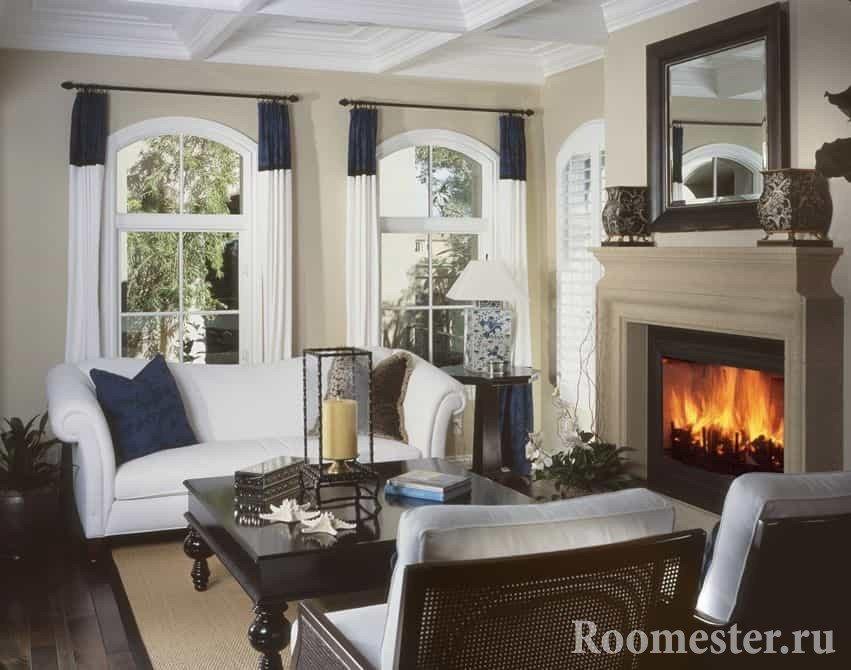 Дизайн гостиной в доме с камином перед диванным уголком