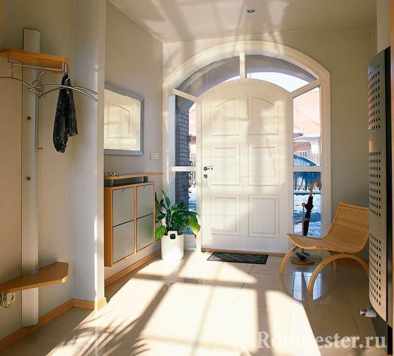 Большая прихожая частного дома - эффектная дверь