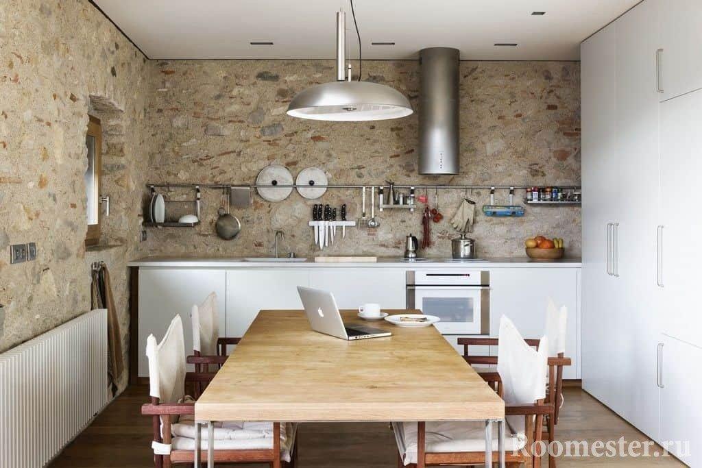 Кухня с бетонными стенами и большим шкафом с обеденной зоной