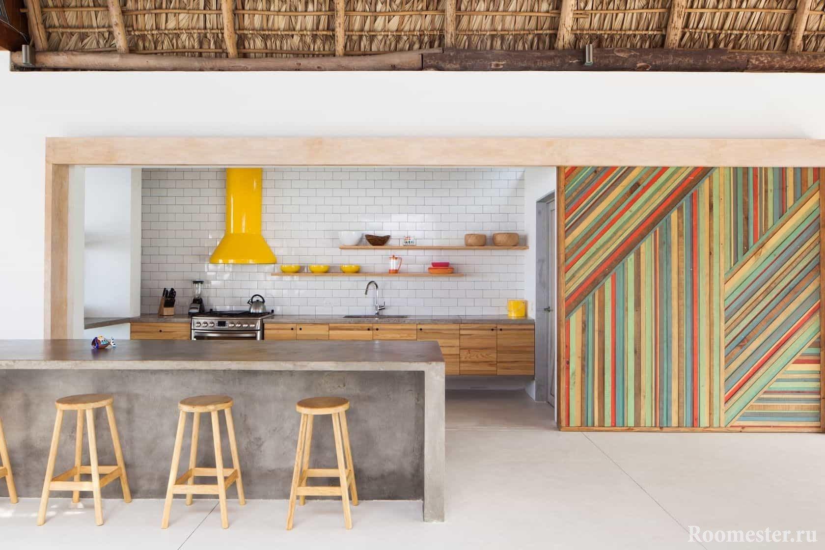 Светлая и яркая кухня в загородном доме с барными стульями у стола