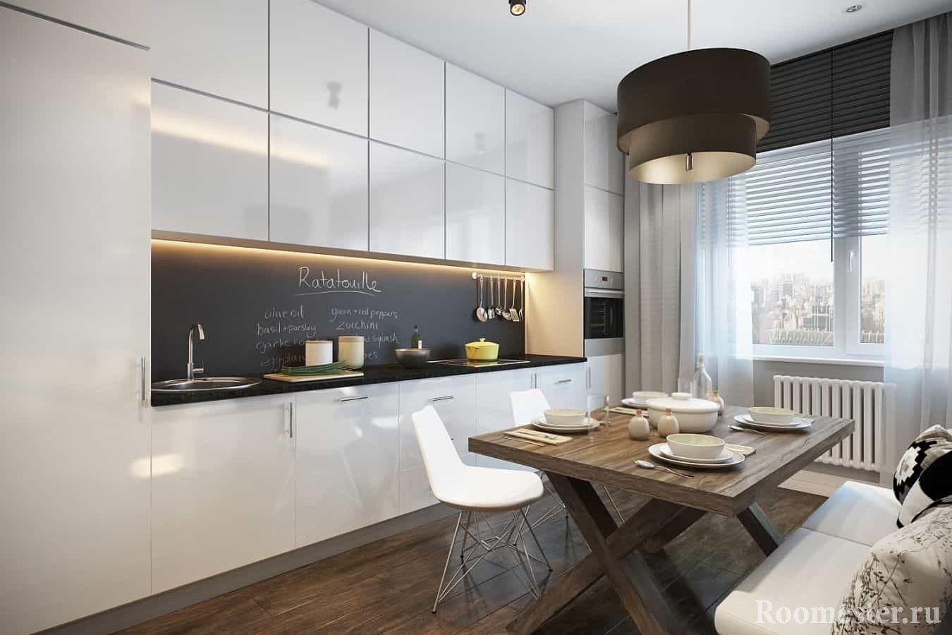Белая шкафа с черным фартуком на кухне с окном