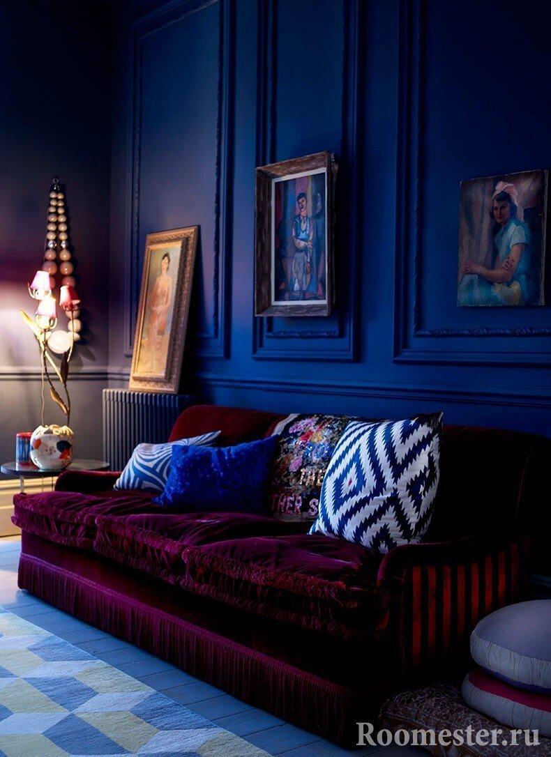 Бордовый диван на фоне темно-синих стен
