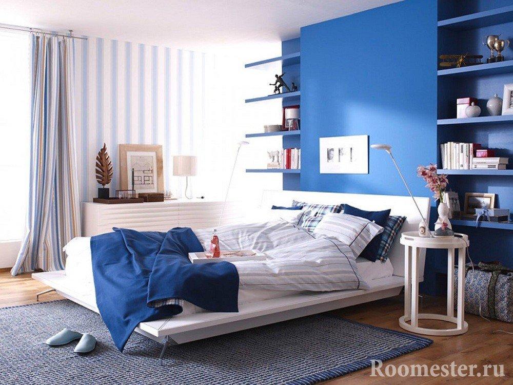 Синяя стена в спальне в сочетании с обоями в полоску