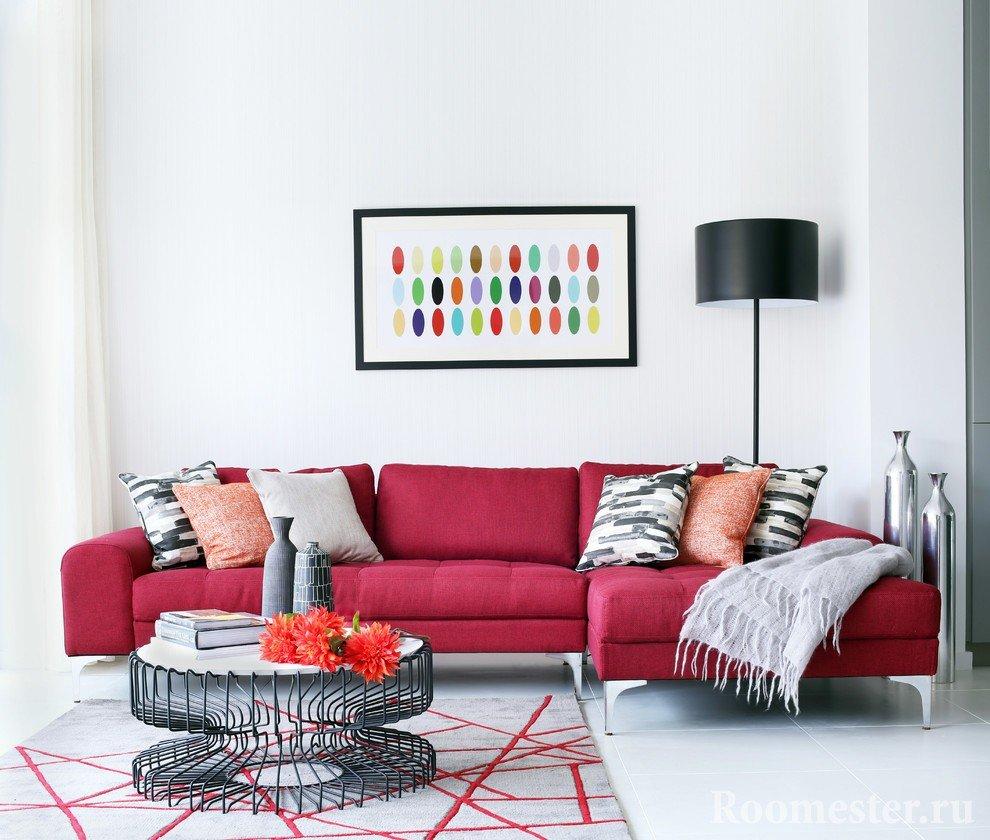 Бардовый диван в комнате с белыми стенами