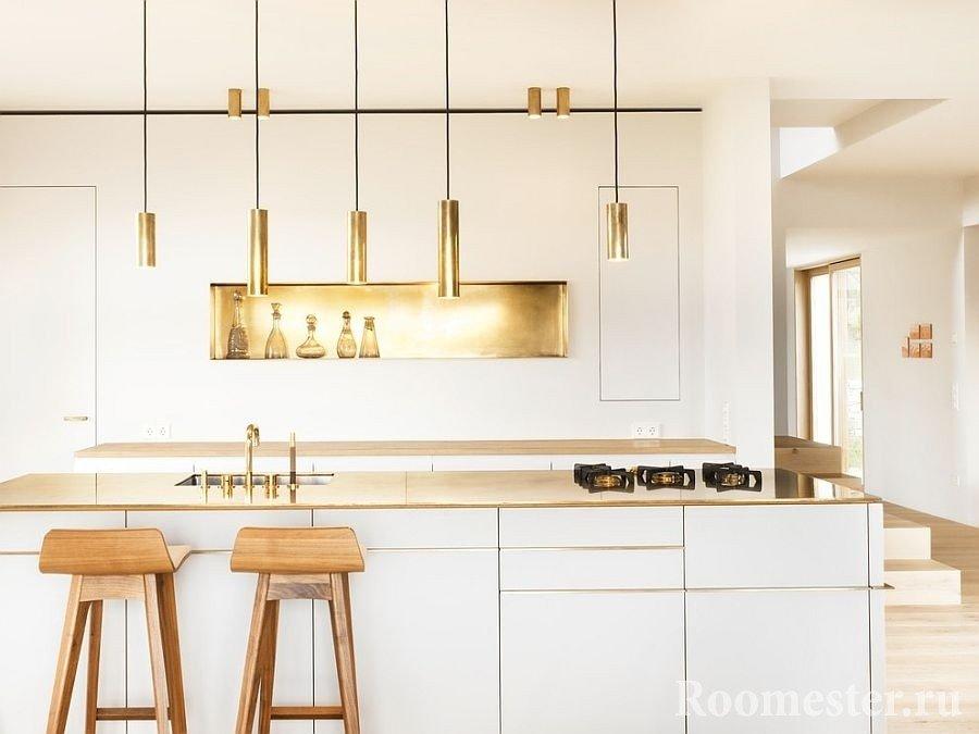 Золотые элементы декора на белой кухне с деревянными барными стульями