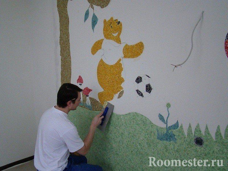 Мужчина рисует Вини-Пуха на стене в детской