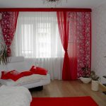Красные шторы, подушки и ковер в сочетании с белыми стенами и мебелью