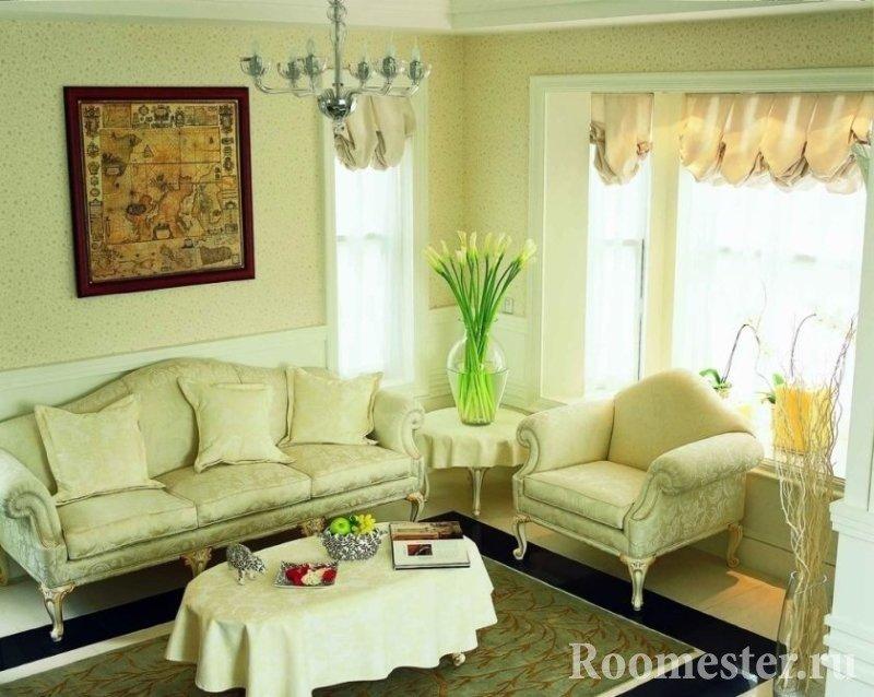 Ваза с цветами на столике между диваном и креслом