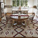 Кухня с белой мебелью и коричневым столом
