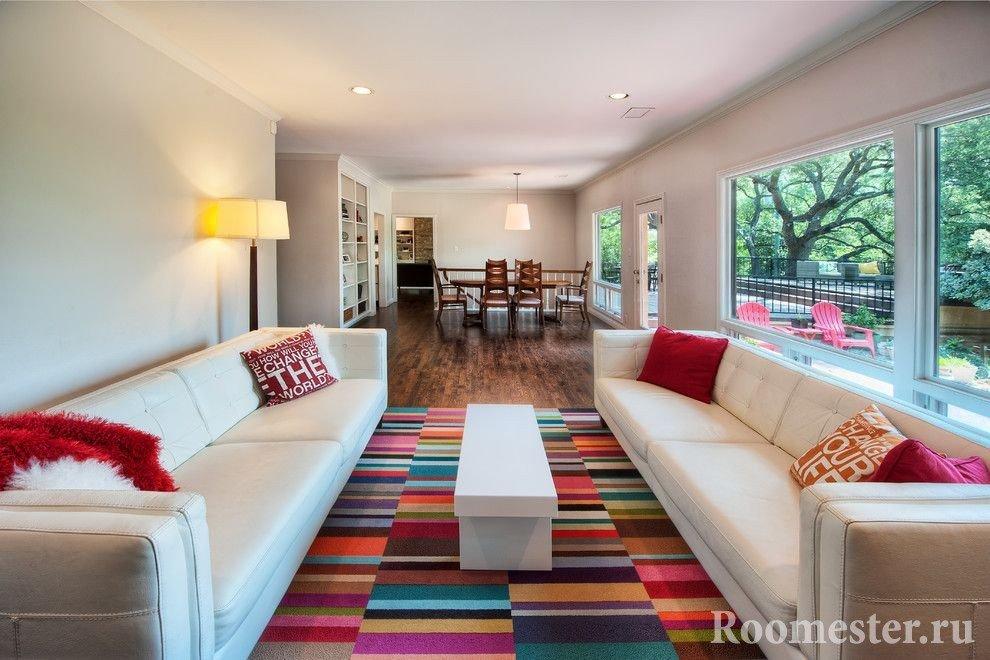 Гостиная с белыми диванами и цветным ковром