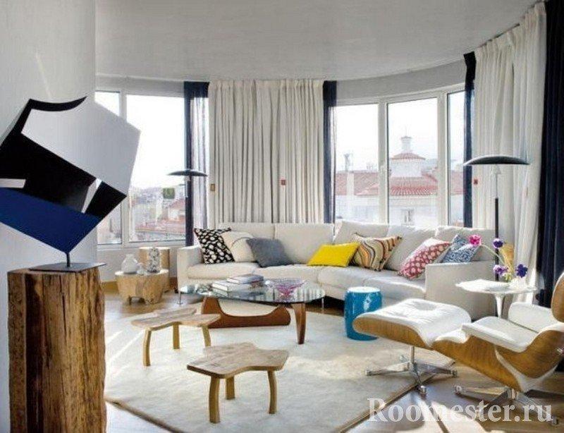 Полукруглая комната с белой и деревянной мебелью