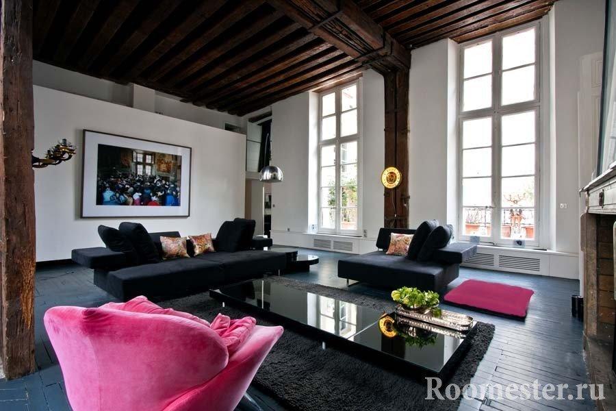 Черные диваны и розовое кресло в комнате