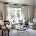 Стеклянный столик перед белыми креслами и диваном