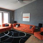 Оранжевая мебель в серой комнате