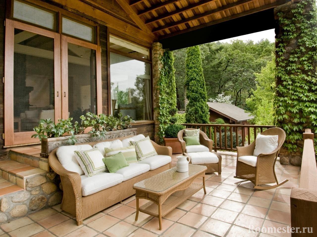 Деревянная мебель с белыми подушками на веранде
