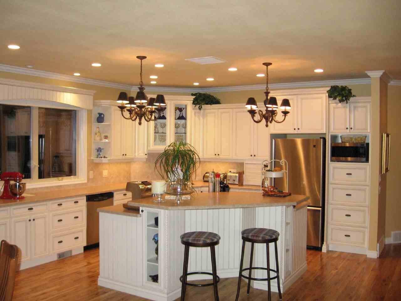 Стальной холодильник и белая мебель на кухне