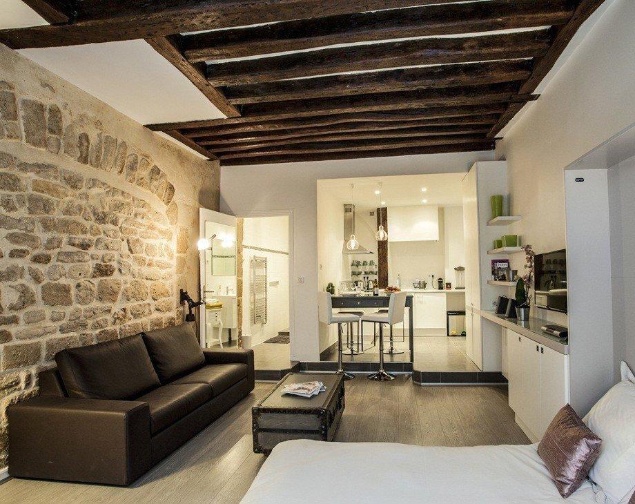 Камень и деревянные балки в интерьере гостиной