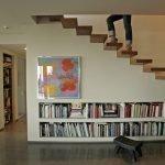 Книжные полки под ступенями в зале