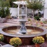 Горшки с цветами вокруг фонтана