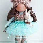 Зайка в руках куклы