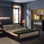 Широкая кровать в спальне c синими стенами