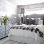 Высокая белая кровать в серой комнате