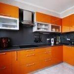 Однотонный черный фартук на оранжевой кухне