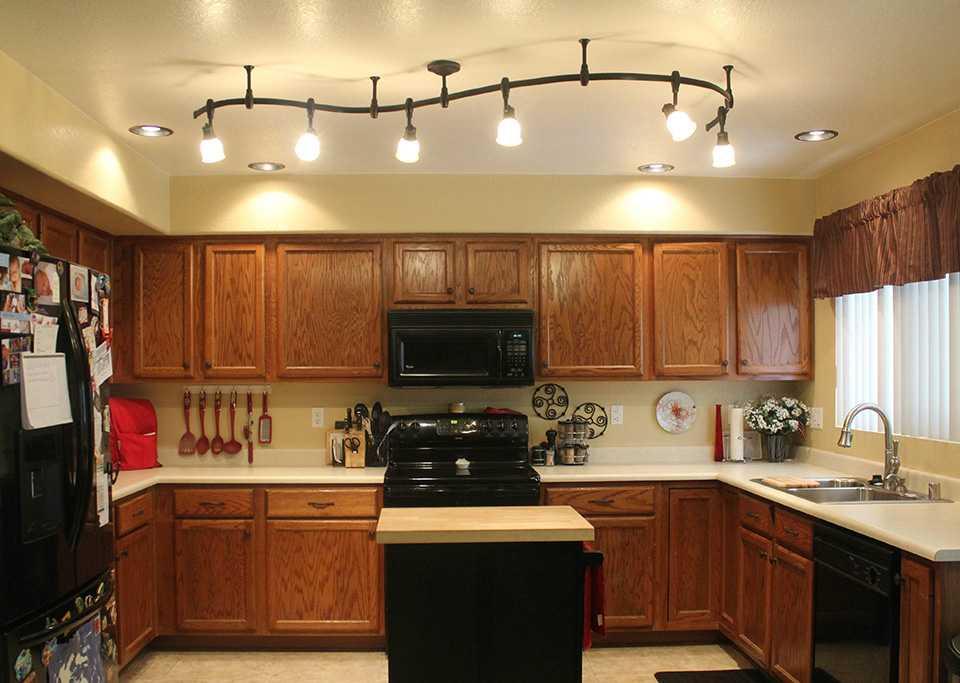 Освещение из люстры и светильников в интерьере кухни