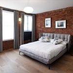 Кирпичная стена и серые шторы в спальне