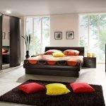 Яркие подушки на ковре в спальне