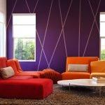 Сочетание сиреневых стен и оранжевого дивана