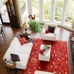 Красный ковер в интерьере гостиной с большими окнами