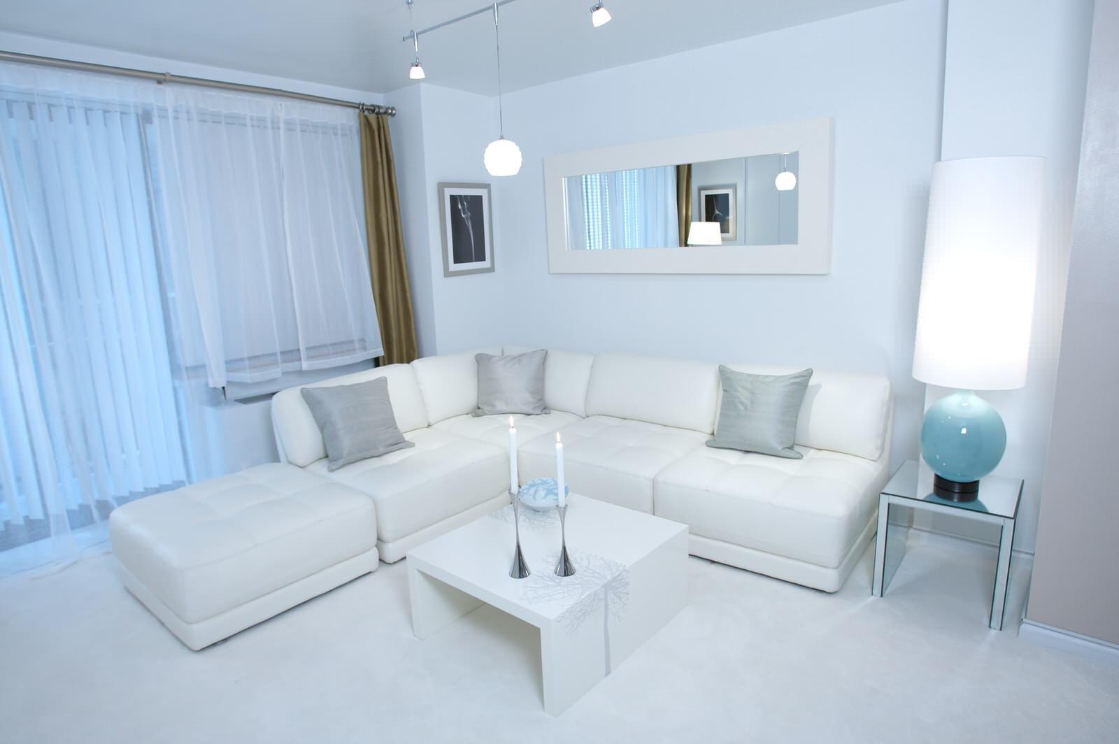 Белый угловой диван с серыми подушками
