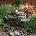 Фонтан в камне, вокруг разные кустарники