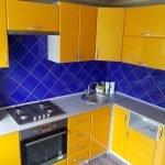 Сочетание синего фартука и желтой мебели