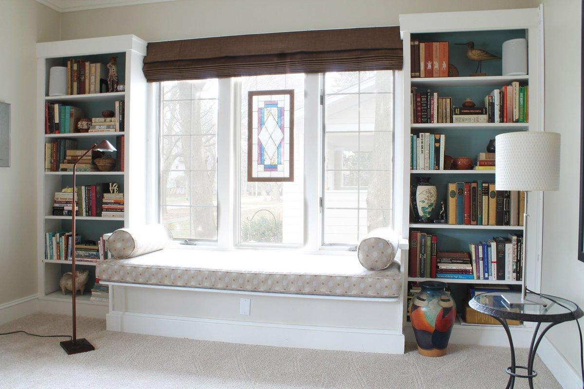 Полки – мини-библиотека в гостиной под окном