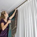 Девушка вешает шторы