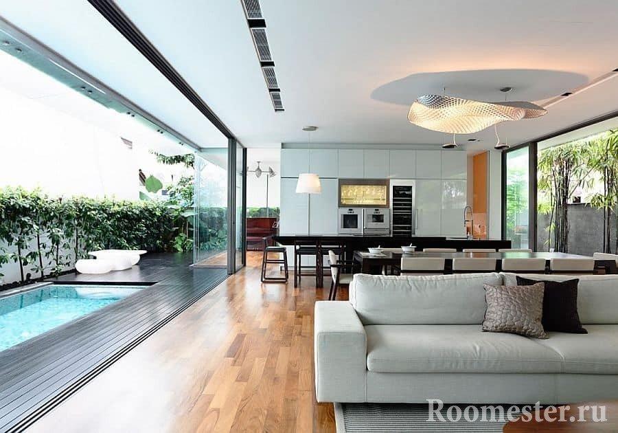 Дизайн кухни-столовой-гостиной со стеной полностью из стекла