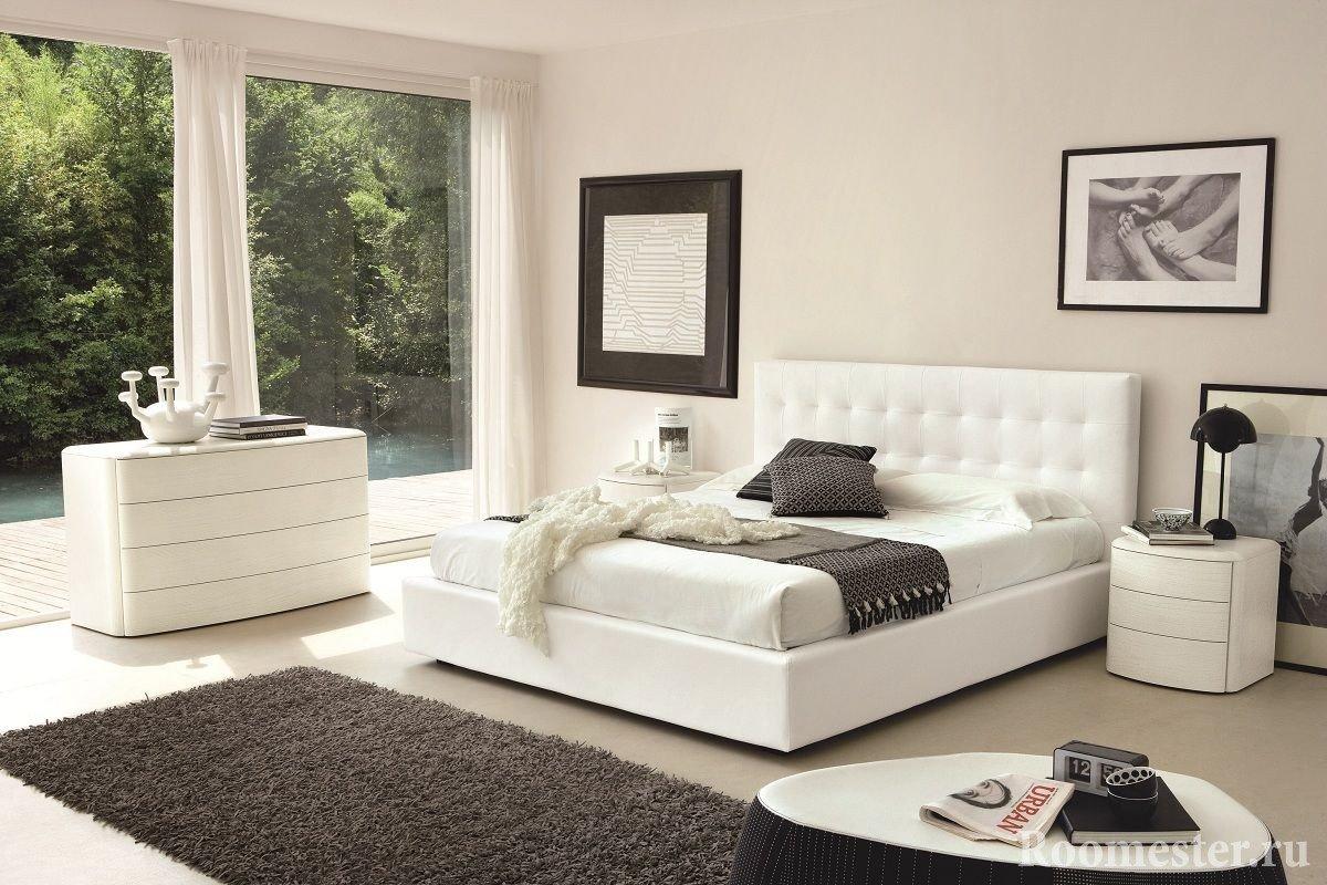 Белые кровать, комод и тумбочка в спальне