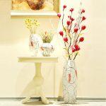 Столик с цветами под картиной на стене