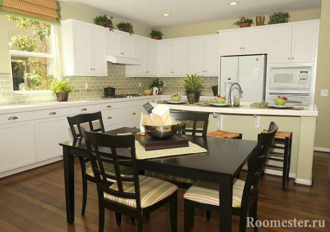 Черный стол со стульями и белая мебель на кухне