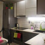 Серый холодильник у окна