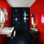 Раковина и зеркало на красной стене