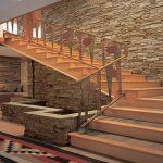 Стены с декоративной плиткой под камень и деревянная лестница