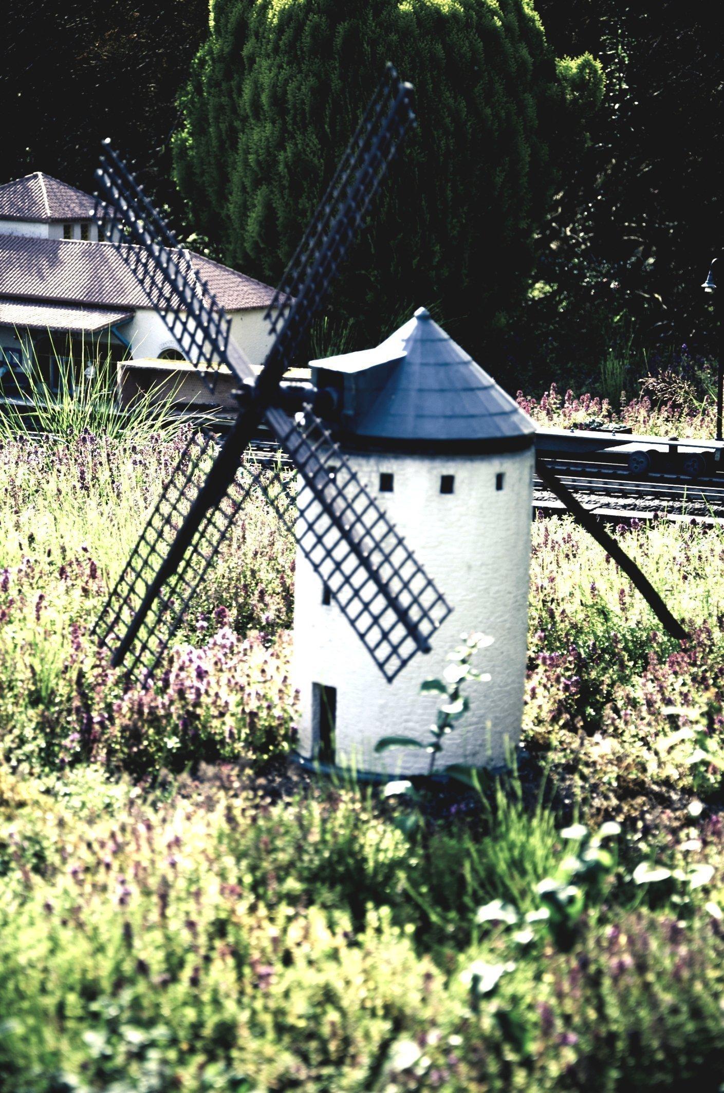 Белая мельница с черными лопастями