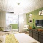 Зеленые стены в спальне с детской кроваткой