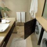Стиральная машинка за дверцей в ванной комнате