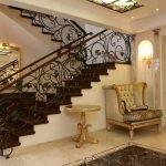 Кресло и столик у лестницы светильник на стене