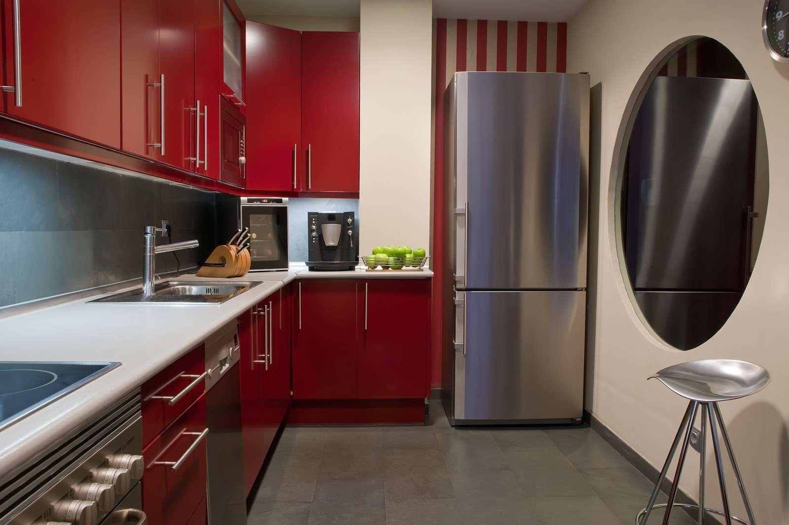 Серый пол на кухне с красной мебелью